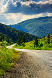 Vertical winding road goes to mountains under a cloudy sky Stock Images