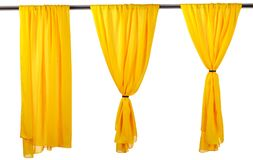 Vertical yellow satin curtains isolated on white. Background royalty free stock photo