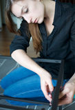 Vertical of a young woman constructing a piece of furniture. Vertical of a woman constructing a piece of furniture Royalty Free Stock Images