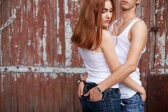 Verticale émotive d'un couple élégant dans des jeans restant ensemble Images stock