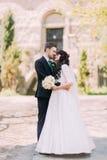 Verticale affectueuse de couples Belle jeune mariée et marié beau posant en parc Vieux bâtiment de vintage au fond Photo libre de droits