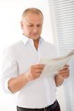 Verticale affichée heureuse de journaux d'homme d'affaires aîné Images stock