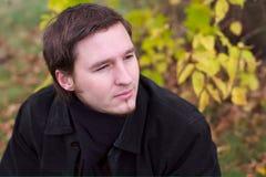 Verticale belle d'homme à l'arrière-plan de lames d'automne Photographie stock libre de droits