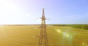 Verticale bewegingsvlucht dichtbij de toren en de machtslijnen van de hoogspanningselektriciteit bij groen en geel gebied stock footage