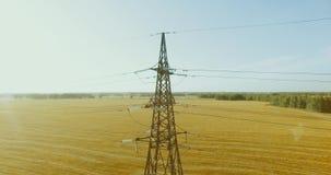 Verticale bewegingsvlucht dichtbij de toren en de machtslijnen van de hoogspanningselektriciteit bij groen en geel gebied stock videobeelden