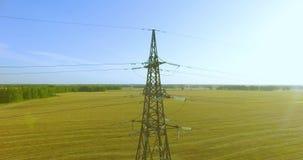 Verticale bewegingsvlucht dichtbij de toren en de machtslijnen van de hoogspanningselektriciteit bij groen en geel gebied stock video