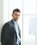 Verticale d'homme d'affaires à l'hublot de bureau Photos stock