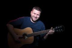 Verticale d'homme de sourire d'A avec la guitare photo libre de droits