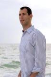 Verticale d'homme de younf à l'océan regardant à gauche Photos libres de droits