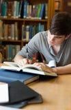 Verticale d'un étudiant bel écrivant un essai Image libre de droits