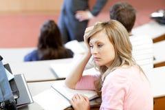 Verticale d'un étudiant féminin ennuyé à l'université photo libre de droits