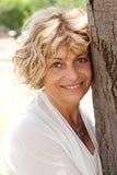 Verticale d'un arbre aîné heureux de fixation de femme Photo stock