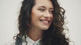 Verticale d'un beau jeune brunette Une fille de couleur claire avec l'amusement de sourire de coiffures hirsutes banque de vidéos