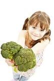 Verticale d'un broccoli de sourire de fixation de jeune fille image libre de droits