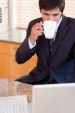Verticale d'un café potable d'homme d'affaires tout en à l'aide d'un ordinateur portable Photos stock