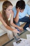 Verticale d'un couple coupant leur carte de crédit Images libres de droits