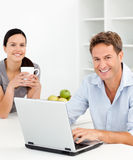 Verticale d'un couple détendant dans la cuisine Image libre de droits