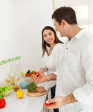 Verticale d'un couple heureux préparant la nourriture Photos libres de droits