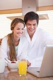 Verticale d'un couple prenant le petit déjeuner tout en à l'aide d'un carnet Photos libres de droits