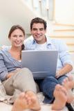 Verticale d'un couple utilisant un carnet tout en se trouvant sur un sofa Photo stock