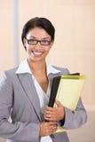 Verticale d'un dépliant de sourire de fixation de femme d'affaires Photo stock