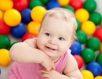 Verticale d'un enfant en bas âge de sourire parmi les billes colorées Images stock