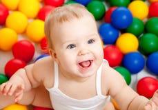 Verticale d'un enfant en bas âge de sourire parmi les billes colorées Photographie stock