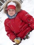Verticale d'un garçon s'asseyant dans la neige Image stock