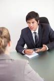 Verticale d'un gestionnaire interviewant un demandeur féminin images stock