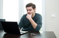 Verticale d'un homme à la maison travaillant sur un ordinateur portatif photos libres de droits