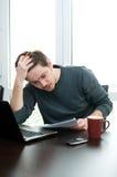 Verticale d'un homme à la maison travaillant sur un ordinateur portatif photos stock