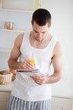 Verticale d'un homme affichant les nouvelles tout en buvant du jus d'orange Photo stock