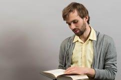 Verticale d'un homme affichant un livre D'isolement sur le gris Image stock