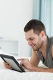 Verticale d'un homme de sourire à l'aide d'un ordinateur de tablette   Photos libres de droits