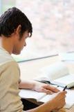 Verticale d'un jeune étudiant écrivant un essai Photographie stock libre de droits