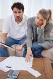 Verticale d'un jeune couple inquiété regardant leurs factures photos libres de droits
