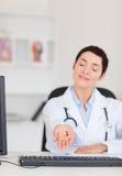 Verticale d'un jeune docteur féminin affichant des pillules Photo libre de droits