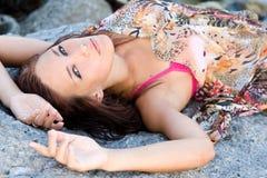 Verticale d'un jeune femme se trouvant sur une roche Image stock