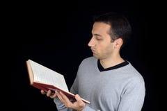 Verticale d'un jeune homme affichant un livre Photos stock