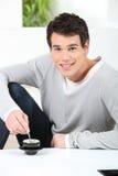 Verticale d'un jeune homme avec la cuvette de café Images stock