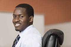 Verticale d'un jeune sourire noir d'homme d'affaires. Photo stock