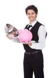 Verticale d'un maître d'hôtel avec le piggybank Photographie stock libre de droits