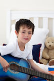 Verticale d'un petit garçon jouant la guitare images libres de droits
