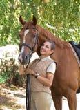 Verticale d'une belle amazone restant avec le cheval à l'extérieur Photos libres de droits