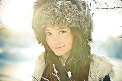 Verticale d'une belle fille dans un chapeau de fourrure dans le backl Photos stock