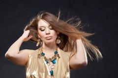 Verticale d'une belle fille dans une robe d'or Photos libres de droits