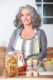 Verticale d'une cuisson aînée de femme image libre de droits