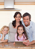 Verticale d'une famille de sourire utilisant un ordinateur de tablette ensemble Photographie stock libre de droits