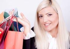 Verticale d'une femme blonde avec des sacs à provisions Photographie stock