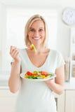 Verticale d'une femme blonde mangeant de la salade mixte Image stock